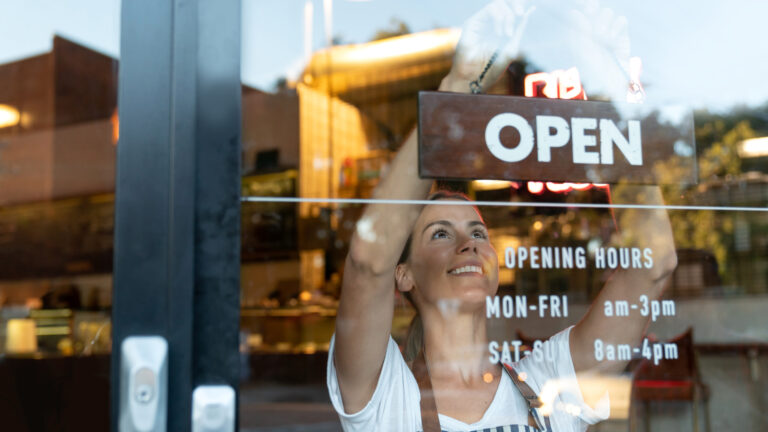 Happy business owner hanging an open sign at a café